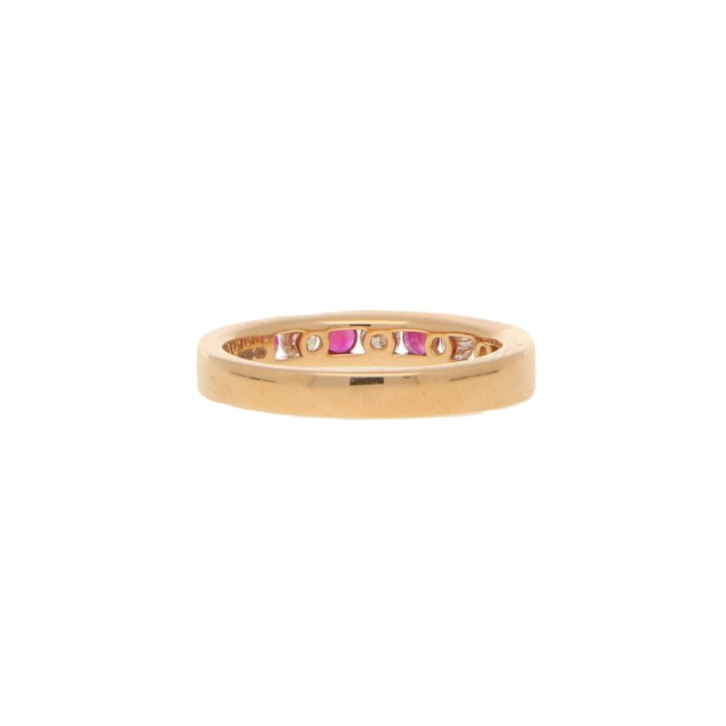 Ruby and diamond half eternity ring in 18k rose gold.
