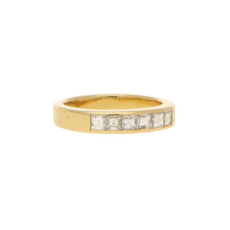 Half diamond eternity ring in 18k yellow gold.